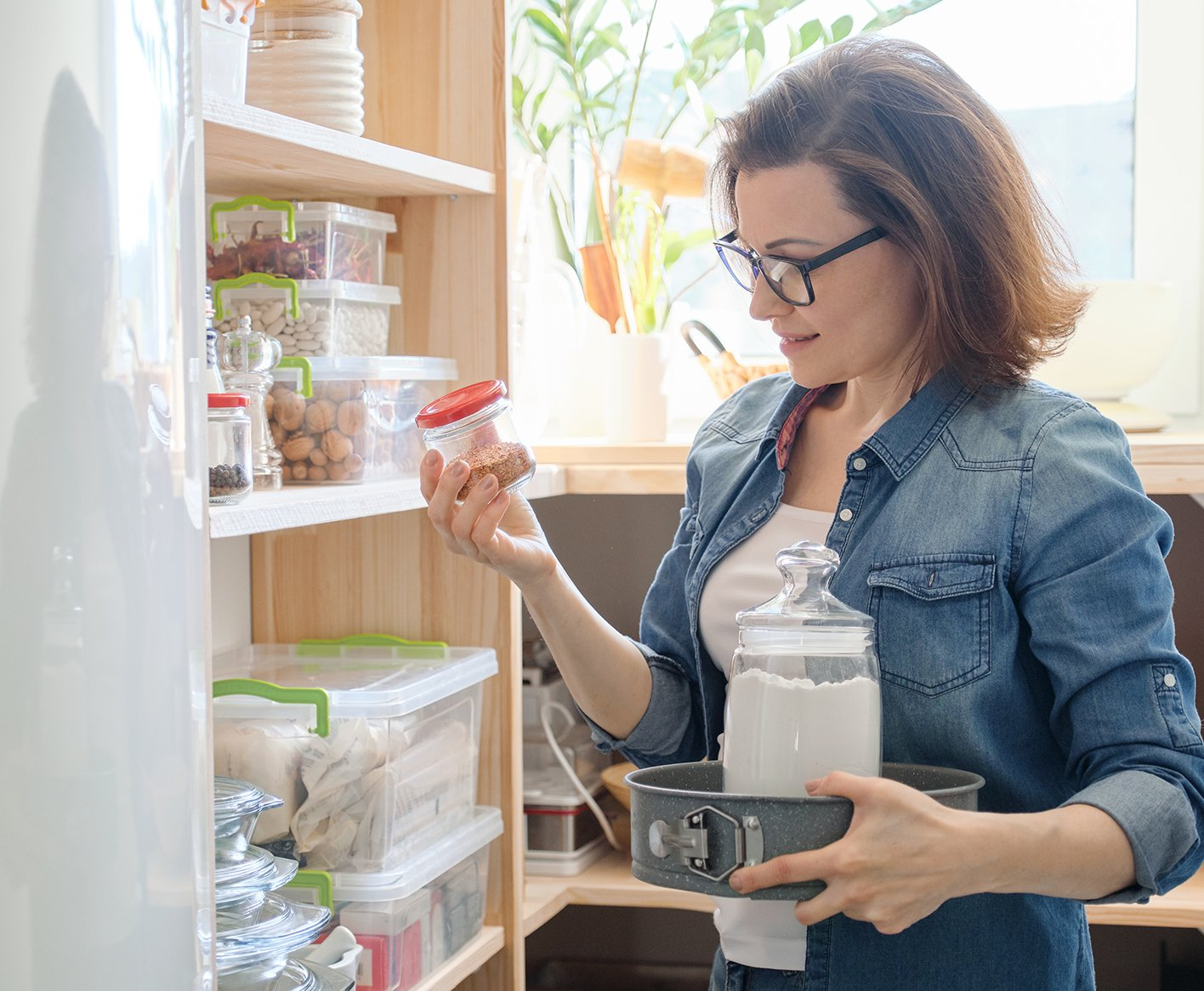 woman stocking pantry after grocery shopping
