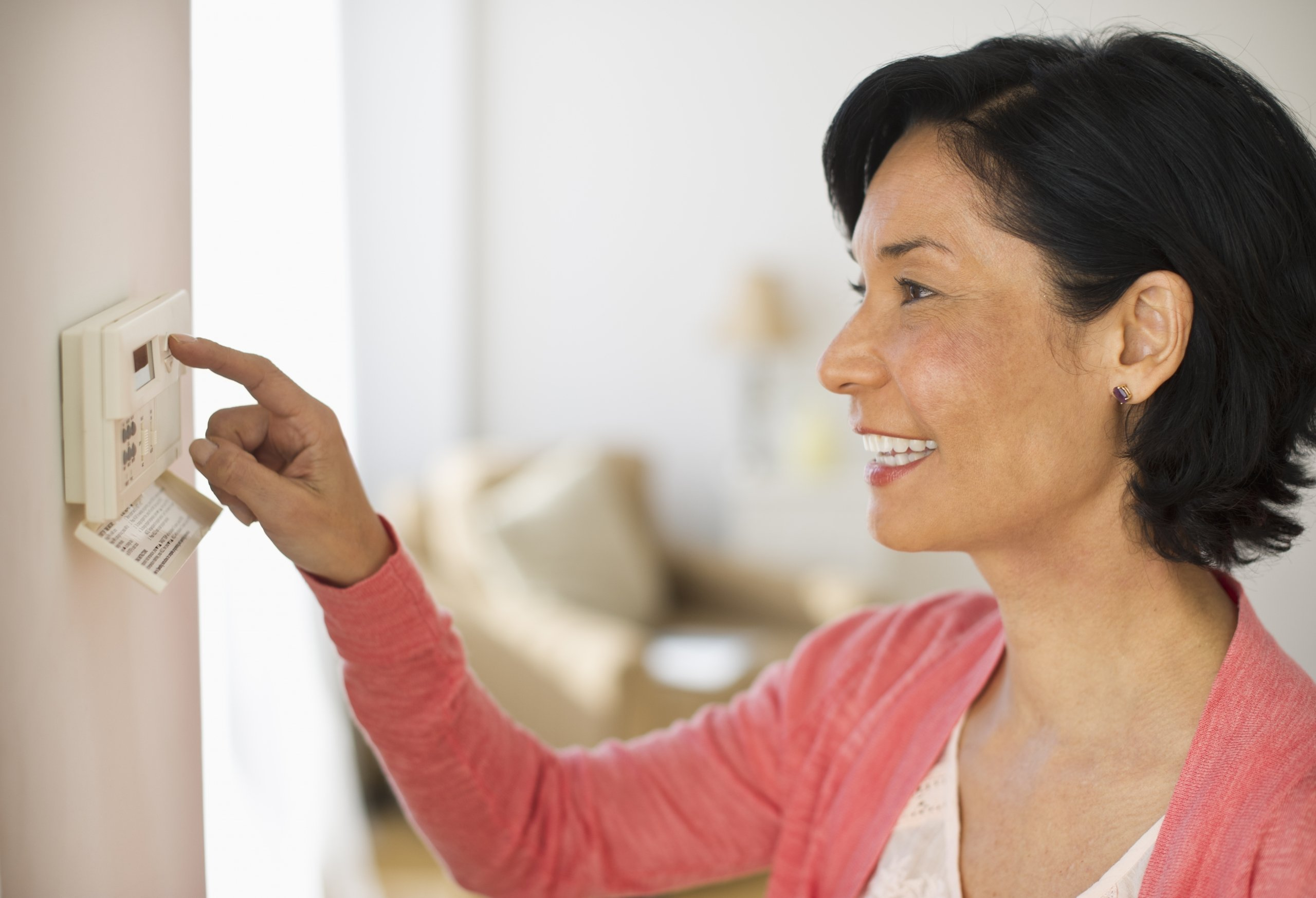 woman checking the thermostat in her home
