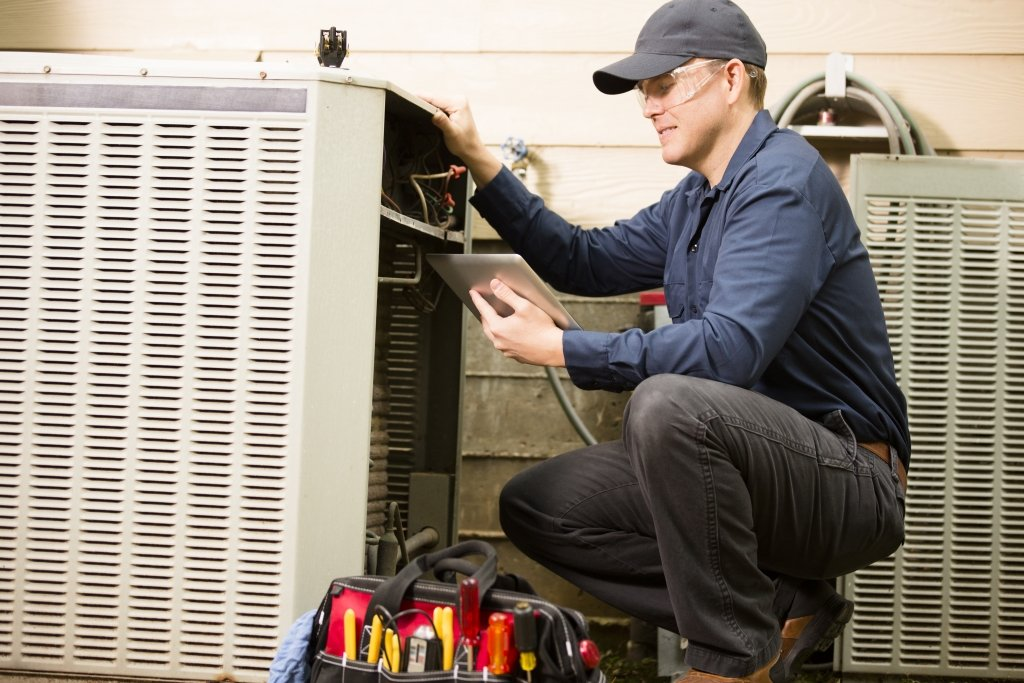 HVAC repairman working on home air conditioning unit
