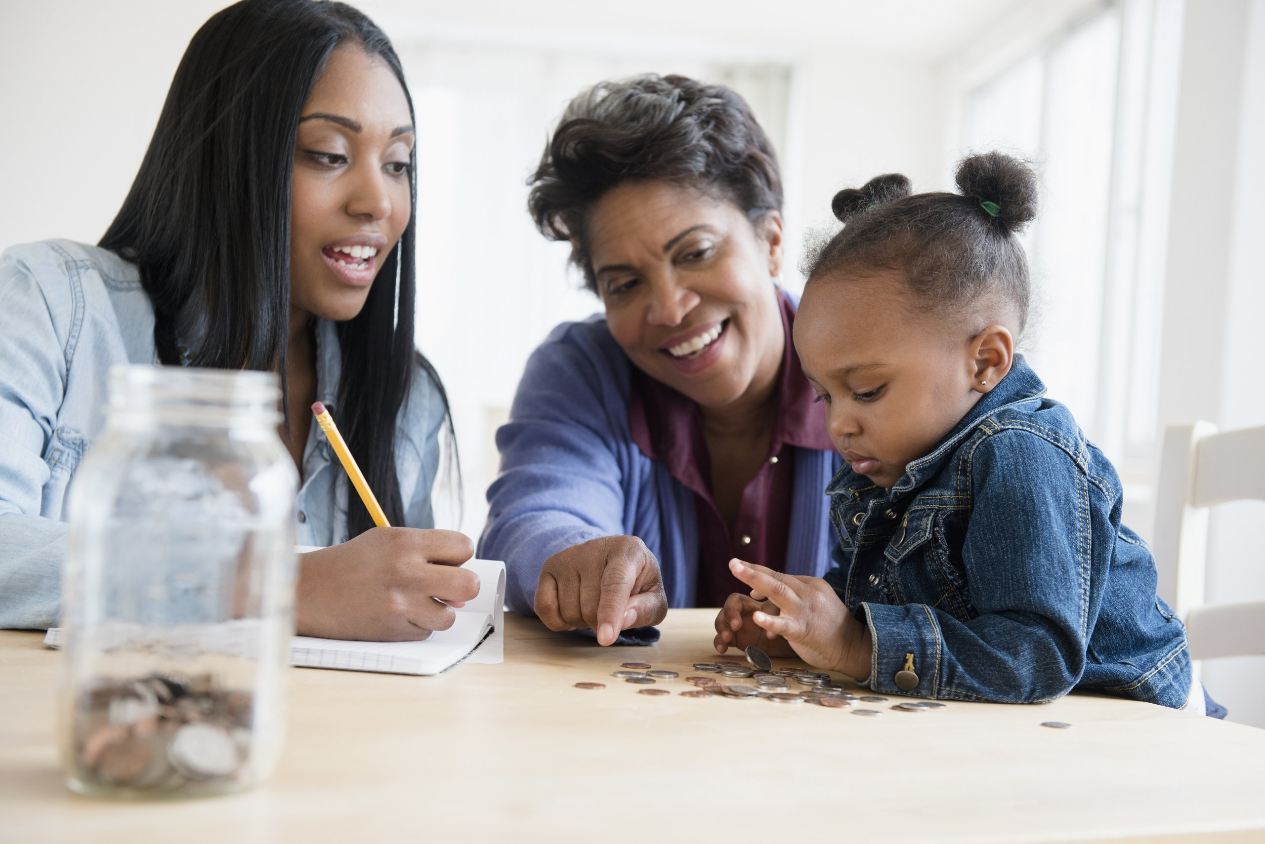 mother and grandmother teaching young girl about managing money