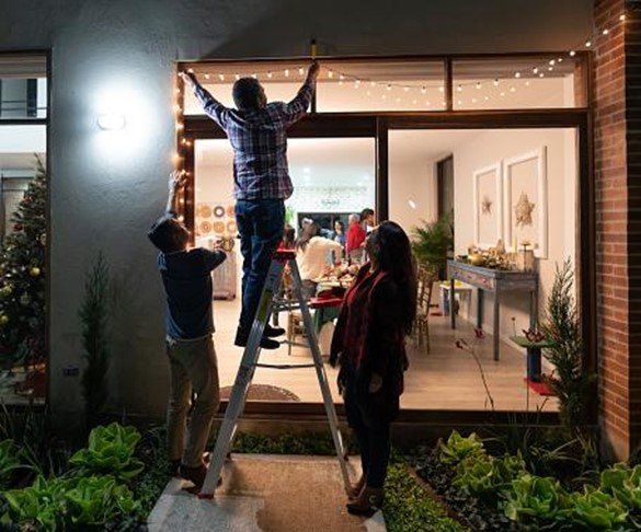 friends hanging string lights outside back door of their home