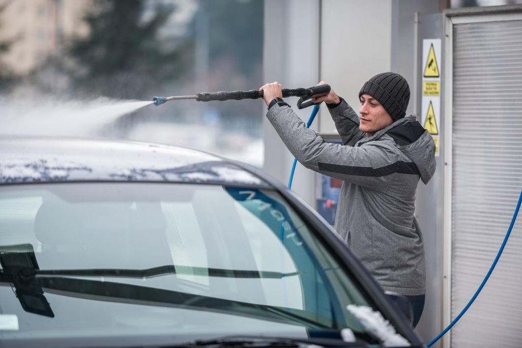Person cleaning car during a winter morning.