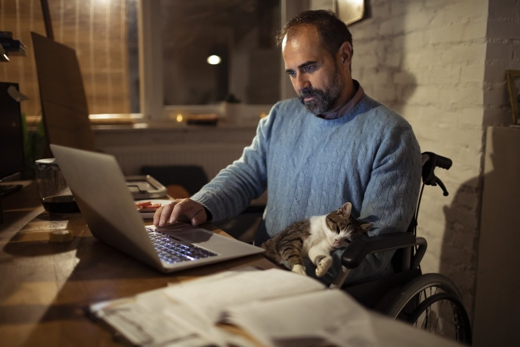 Man holding a sleepy cat on his lap